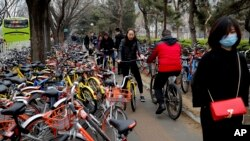 Residents ride bicycles from bike-sharing company Ofo try to pedal through a sidewalk crowded with bicycles from the bike-sharing companies Ofo, Mobike and Bluegogo, near a bus stand in Beijing, China, March 23, 2017. As many as 2.2 million of these two-wheelers have been deployed, which are available for rent for as little as U.S. 7 cents for half an hour, in the latest symbol of heavy spending in China's internet sector where startups are in a race to attract more users to their services.