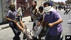 也门的反政府示威者抬着在塔伊兹抗议中受伤的同伴