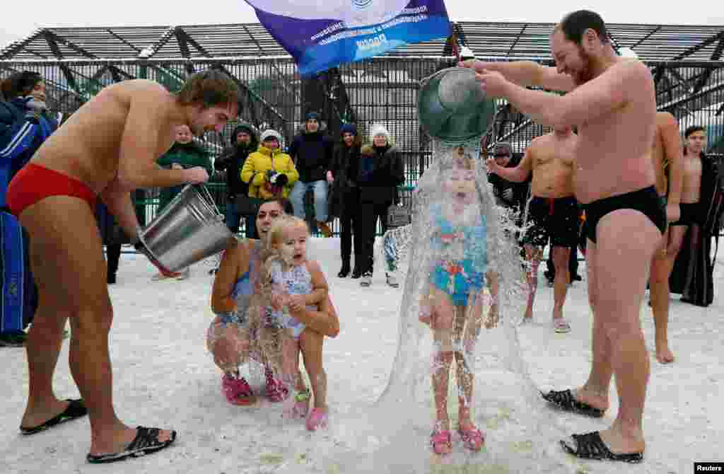Visitors watch as members of a local winter swimmers club pour buckets of cold water over their daughters, 7-year-old Liza Broverman and 2-year-old Alisa Smagina, during a celebration of Polar Bear Day at the Royev Ruchey zoo, with the air temperature at about minus 5° C (23° F), in Krasnoyarsk, Russia.