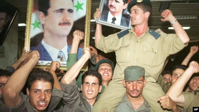 Syrian army soldiers waved portraits of Bashar al-Assad in Damascus in July, 2000, when he became president.