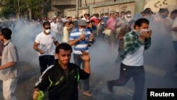 Demonstran anti pemerintah berlarian di jalanan Kornish El Nile, dekat Lapangan Tahrir di Kairo setelah polisi Mesir menembakkan gas air mata (6/10).