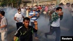 이집트 수도 카이로에서 전투경찰이 최루탄을 발사하자, 시위자들이 흩어지고 있다.