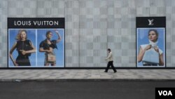 在中國湖北省武漢市,一名男子帶著口罩走過法國奢飾品牌路易威登(Louis Vuitton)的一家門店。 (2020年2月25日)