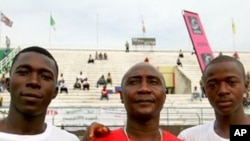 Larry Sawyer and Samba Koroma pose with their coach before a match against Nigeria's youth team at Freetown's national stadium, 09 Dec 2009