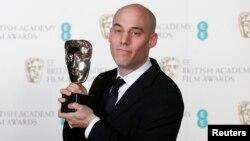 """Joshua Oppenheimer dengan piala film dokumenter terbaik untuk filmnya """"The Act Of Killing"""" pada acara British Academy of Film and Arts (BAFTA) di Royal Opera House, London (16/2). (Reuters/Suzanne Plunkett)"""