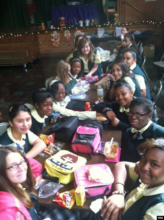 Students at Saint Camillus Catholic school enjoy lunch together in the school building damaged after Superstorm Sandy. (VOA/A. Phillips)