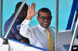 File - Maldives former President Mohamed Nasheed waves from a boat as he is taken back to Dhoonidhoo prison after a court dismissed his appeal against his arrest in Male, March 2015.