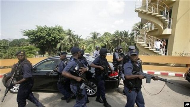 South African police officers stand guard around a car transporting President Jacob Zuma, as he leaves following a meeting with Ivory Coast's internationally-recognized president, Alassane Ouattara, at the Golf Hotel in Abidjan, Ivory Coast, February 22,