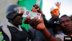 Un hombre muestra su documento de identificación mientras los votantes empujan ansiosos por entrar al centro de votación.