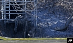 FILE - A pipe from the Dan River Power Plant where coal ash spilled is seen along the Dan River in Eden, N.C., Feb. 5, 2014.