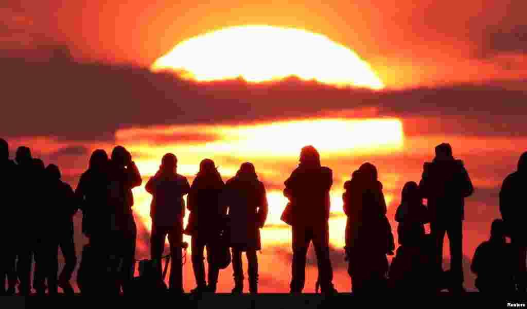 People watch the first sunrise on New Year's Day at Yuriage district in Natori, Miyagi prefecture, Japan, in this photo taken by Kyodo.