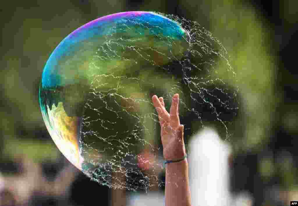 A boy bursts a soap-bubble at Gorky Park in Moscow, Russia.