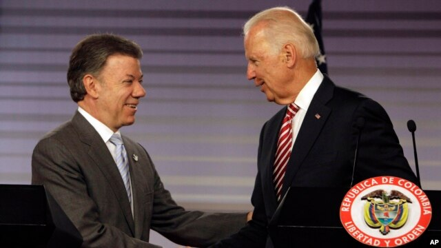 U.S. Vice President Joe Biden, right, shakes hands with Colombia's President Juan Manuel Santos after giving a joint news conference at the presidential palace in Bogota, Colombia, June 18, 2014