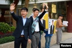 조슈아 웡(왼쪽) 홍콩 데모시스토당 비서장이 구의원 선거 전날인 23일 거리에서 켈빈 람(가운데) 후보 지원 유세를 하고있다.