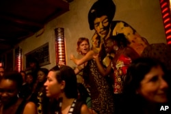 FILE - People dance along to a performance by band Wato in a bar in Saint-Louis, Senegal.