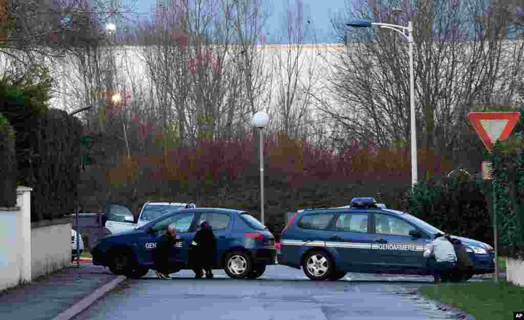 French security officers take cover behind vehicles as they surround a building in Dammartin-en-Goele, northeast of Paris, where the two brothers suspected in a deadly terror attack were cornered, Jan. 9, 2015.