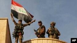 سربازان عراقی بعد از آزادسازی مناطق نزدیک به موصل، پرچم عراق را بالای بردند.
