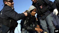 A man (c) who fled the unrest in Tunisia is helped by the Italian police after arriving at the southern Italian island of Lampedusa March 24, 2011