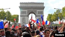France fans react on the Champs-Elysees avenue during their World Cup final
