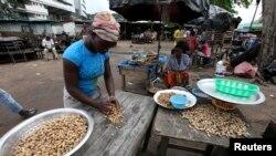 Des Ivoiriennes rassemblent des cacahuètes sur le marché local de Treichville, près d'Abidjan, le 2 novembre 2010.