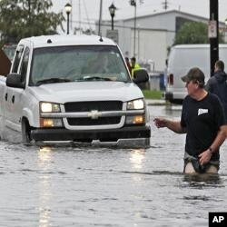 A man guides a truck through the flood waters caused by Tropical Storm Lee in New Orleans, Saturday, Sept. 3, 2011.