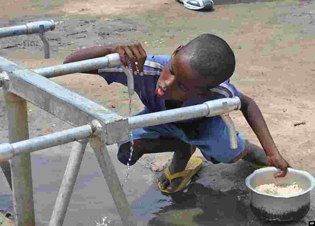 Boy slurps a few drops of water from faucet at Badbaado IDP camp, Mogadishu, Somalia, August 11, 2011. (VOA - P. Heinlein)
