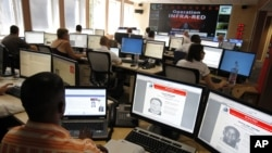FILE - Interpol employees work in the control room of the Infra-Red operation in Lyon, central France. A Nigerian national identified only as Mike, an alleged leader of an email scamming network, was arrested in Port Harcourt, Nigeria, in June, 2016.
