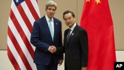 U.S. Secretary of State John Kerry, left, shakes hands with Chinese Foreign Minister Wang Yi as they pose for photos before their meeting at the 47th ASEAN Foreign Ministers' Meeting in Naypyitaw, Myanmar, Aug. 9, 2014.