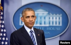 President Barack Obama listens as he participates in his last news conference of the year