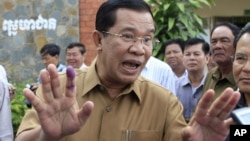 Cambodian Prime Minister Hun Sen gestures with an inked finger after casting his ballot in local elections at Ta Khmau town, in Kandal province, some 15 kilometers (9 miles) south of Phnom Penh, Cambodia, Sunday, June 3, 2012.