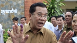 Cambodian Prime Minister Hun Sen gestures after casting his ballot in local elections at Ta Khmau town, in Kandal province.