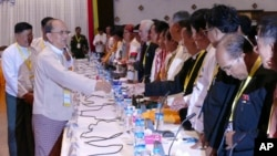 Myanmar President Thein Sein, front left, greets representatives of political parties during a meeting at Yangon region government office, Nov. 15, 2015.