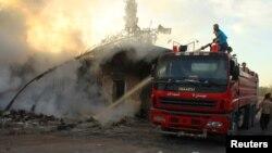 20일 시리아 알레포 서부 반군 점령 마을인 우름알쿠브라에서 한 민방위 대원이 공습으로 일어난 불을 끄고 있다.