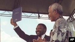 Presidente da Assembleia Constituinte sul-africana, Cyril Ramaphosa, mostrando um exemplar da nova constituição da África Sul pouco depois de rubricada pelo então presidente Nelson Mandela, Dezembro de 1996