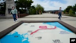 Visitors walk by a map of two Koreas showing North Korea's capital, Pyongyang, and South Korea's capital, Seoul, at the Imjingak Pavilion in Paju, near the border with North Korea, South Korea, Sept. 24, 2021.
