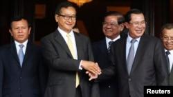 Tokoh oposisi Kamboja Sam Rainsy berjabat tangan dengan Perdana Menteri Hun Sen (kanan) - (foto: dok).