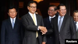 Cambodia's Prime Minister Hun Sen (2nd R) shakes hands with Sam Rainsy (2nd L), president of the Cambodia National Rescue Party (CNRP), after a meeting at the Senate in central Phnom Penh July 22, 2014. Sen and Rainsy met at the Senate in an attempt to solve the country's year-long political crisis after a disputed election. Seven members of parliament and an assistant, all members of CNRP, were ordered detained pending trial and taken to prison on charges of leading an insurrection, which carries a penalty of 20 to 30 years in prison, and incitement to violence. REUTERS/Stringer