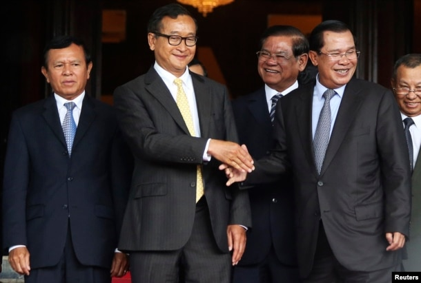 Cambodia's Prime Minister Hun Sen (2nd R) shakes hands with Sam Rainsy (2nd L), president of the Cambodia National Rescue Party (CNRP), after a meeting at the Senate in central Phnom Penh July 22, 2014.