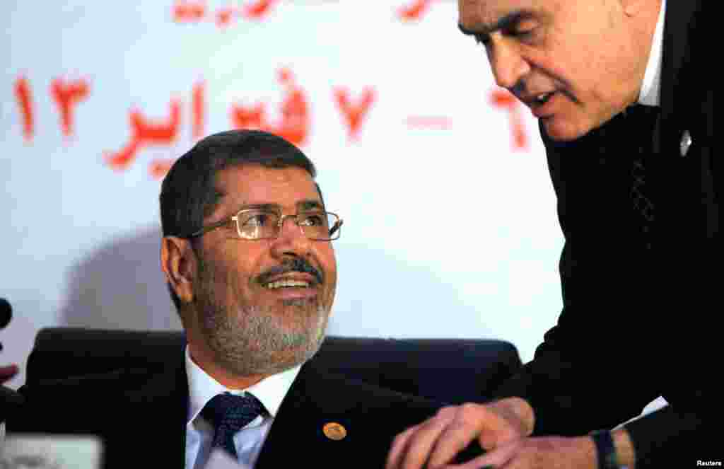 Egyptian President Mohammed Morsi listens to his Foreign Minister Mohammed Kamel Amr during the opening of the 12th summit of the Organization of Islamic Cooperation (OIC) in Cairo, Egypt, February 6, 2013.