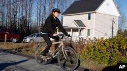 La enfermera Kaci Hickox pasea en su bicicleta en una carretera rural de Fort Kent, Maine, en desafío a su cuarentena.