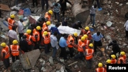 Rescue workers recover body from debris on site of a collapsed residential building, Mumbai, Sept. 28, 2013.
