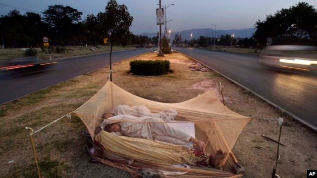 FILE - Vehicles move past Pakistani day laborers sleeping under a mosquito net in the middle of a road in Islamabad, Pakistan.