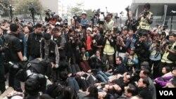 大批留守者手撓手半躺在地上等候警察拘捕(美國之音特約記者湯惠芸攝)
