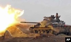 This frame grab from video provided Nov. 8, 2017, by the government-controlled Syrian Central Military Media, shows a tank firing on militants' positions on the Iraq-Syria border.
