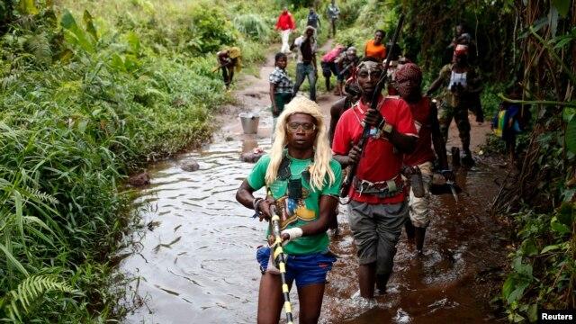 FILE - Members of the anti-Balaka, a Christian militia, patrol outside the Central African Republic village of Zawa April 8, 2014.