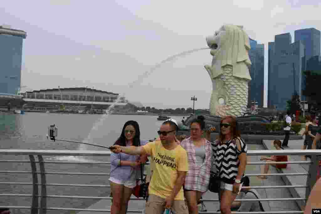 چند گردشگر مقابل مجسمه شیری که نماد ملی سنگاپور است، عکس می گیرند.