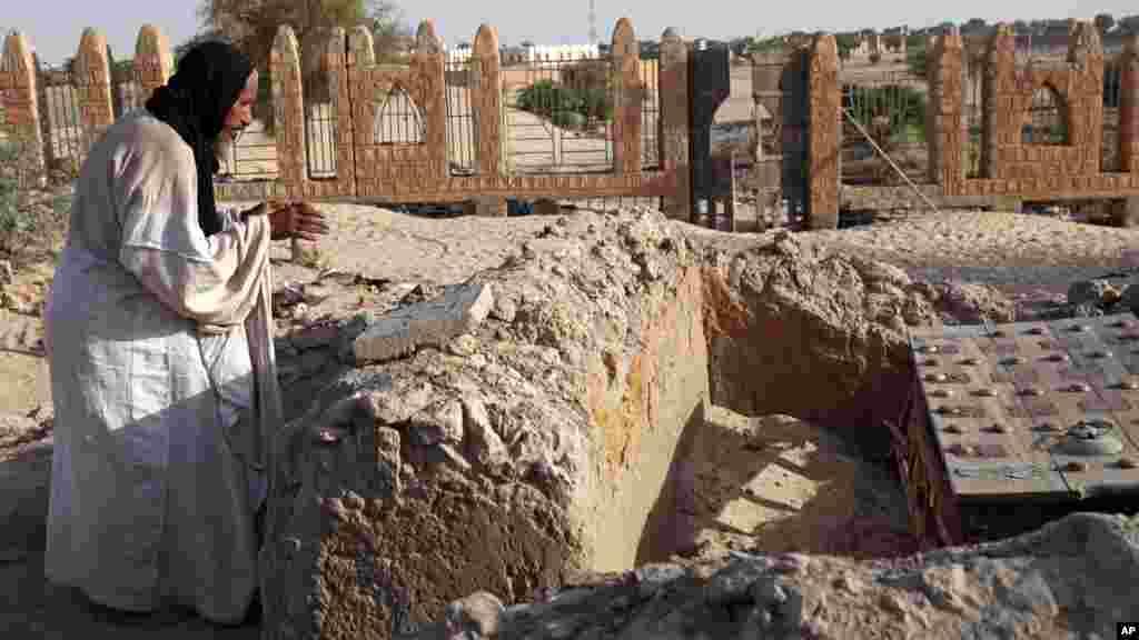 Mohamed Maouloud Ould Mohamed, le preneur de soin des tombes de Tombouctou, prie sur l'une des tombes, le 4 avril 2014.