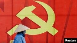Một phụ nữ đi qua poster quảng bá Đại hội Đảng 13 sắp tới tại Hà Nội. Việt Nam sắp chọn ra những lãnh đạo mới trong lúc Mỹ vừa có chính quyền mới sau khi ông Joe Biden bước vào Nhà Trắng.