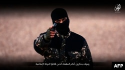 FILE - An image taken from a video published by the media branch of the Islamic State (IS) group on Jan. 3, 2016, purportedly shows an IS fighter at an undisclosed location before executing five men from the Syrian city of Raqa.