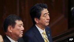 PM Jepang Shinzo Abe (kanan) bersama Menteri bidang isu-isu regional Shigeru Ishiba saat menghadiri sidang parlemen di Tokyo (21/11).
